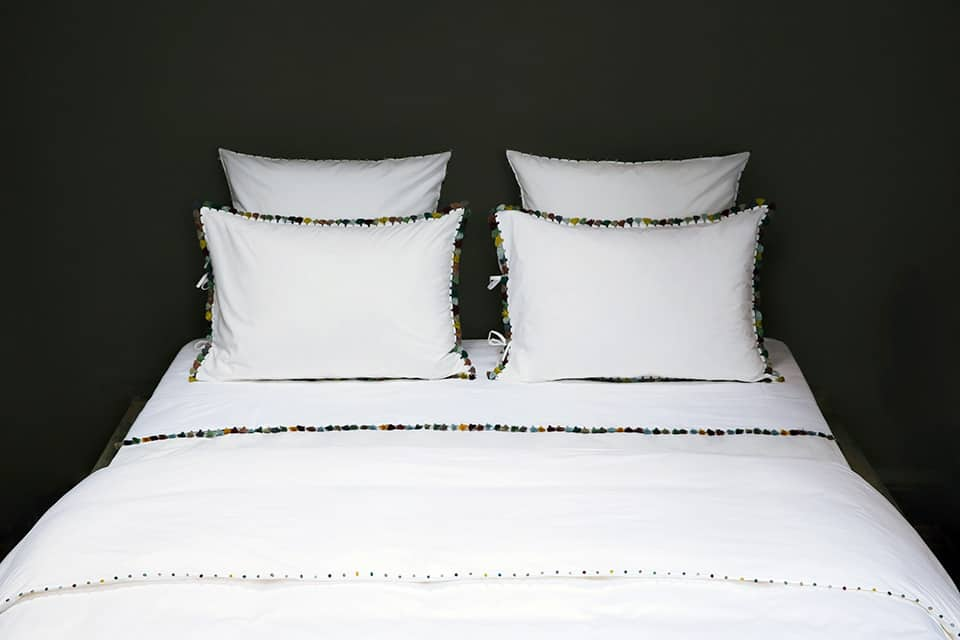 slow bed linen with pompoms made of mercerized combed cotton poplin