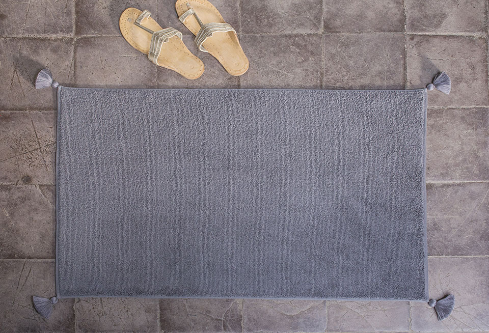 high end grey bath mat with pompoms