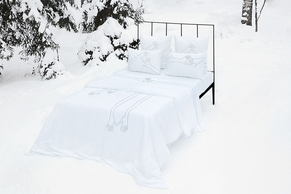 Hand embroidered luxury bed linen in snow landscape Photo Tania Panova