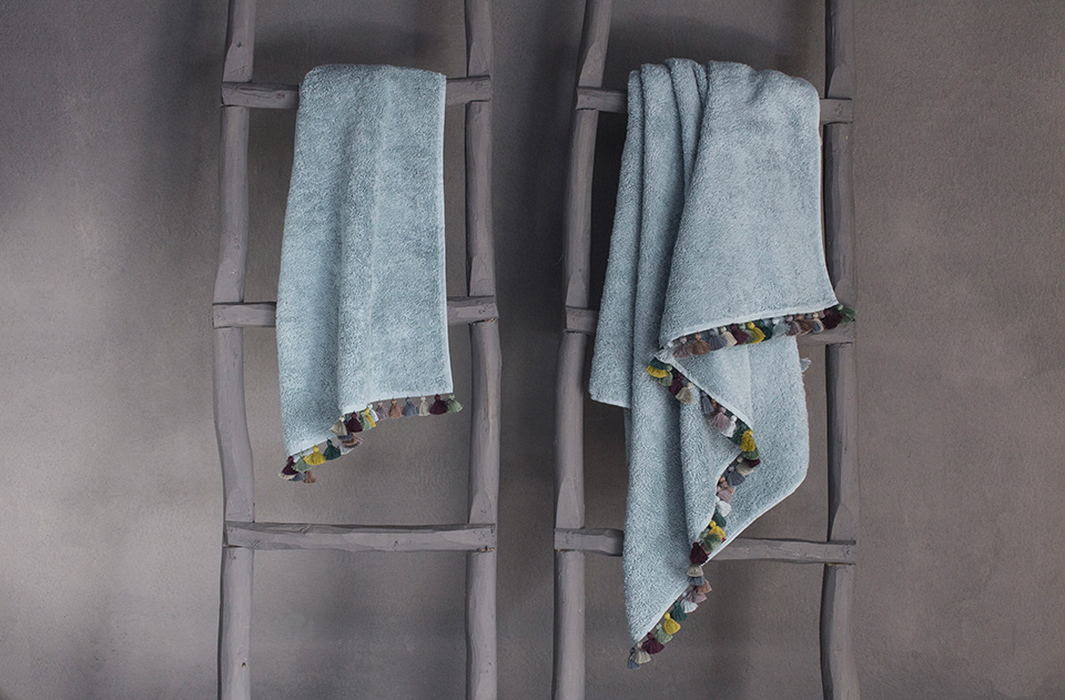 Light blue bath towel collection with multicolor pompoms by Valerie Barkowski